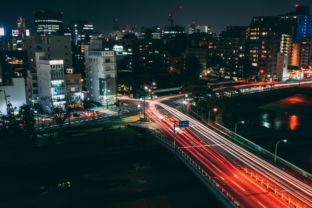 time lapse photography of moving vehicles on road at night