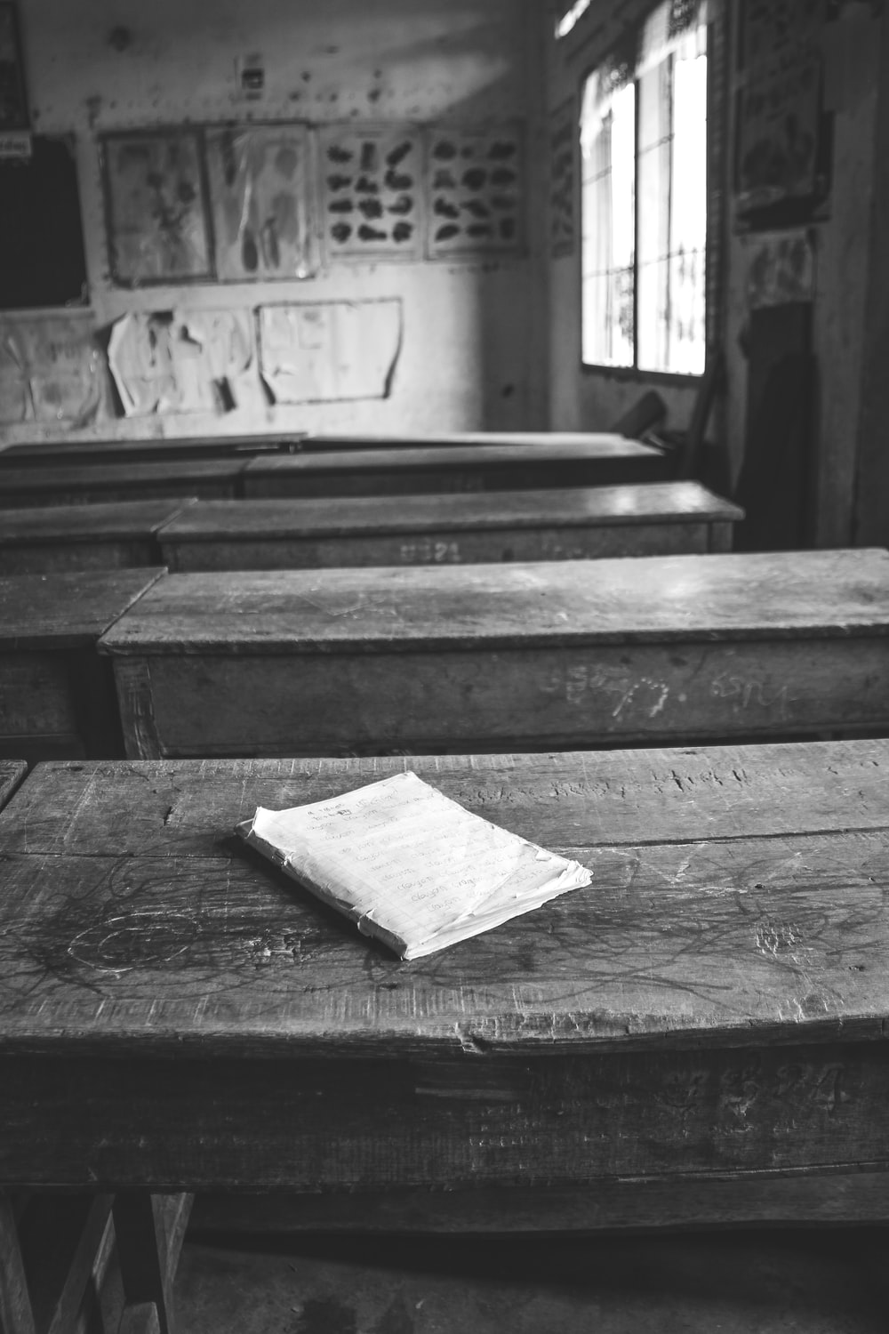 grayscale photo of book on wooden table