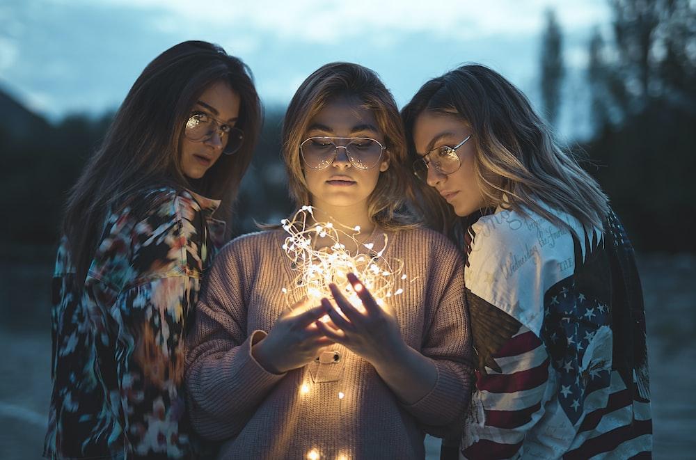 three women near string lights