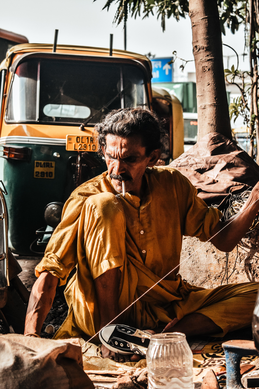 man sitting on floor near rickshaw during daytime