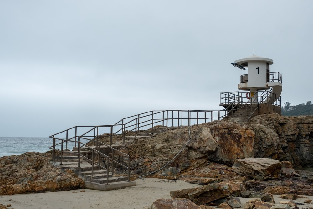 watch tower on rock formation facing ocean