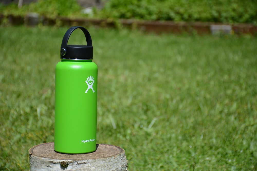 green Hydro Flask tumbler on wood slab
