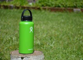 green Hydro Flask tumbler on wood slab