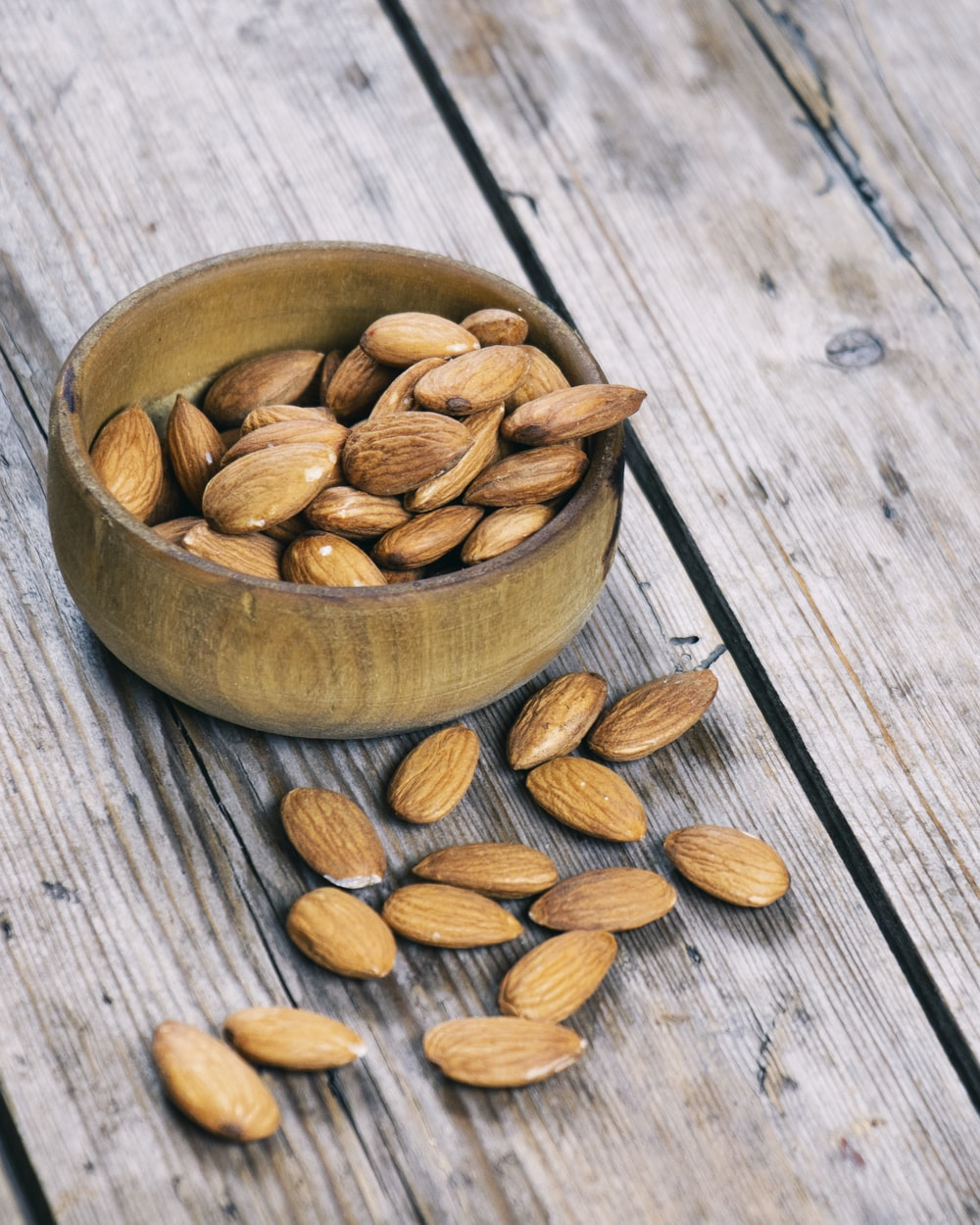 almond nuts in bowl and on table