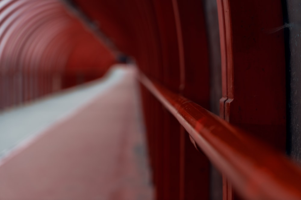 selective photo of red metal bar in tunnel