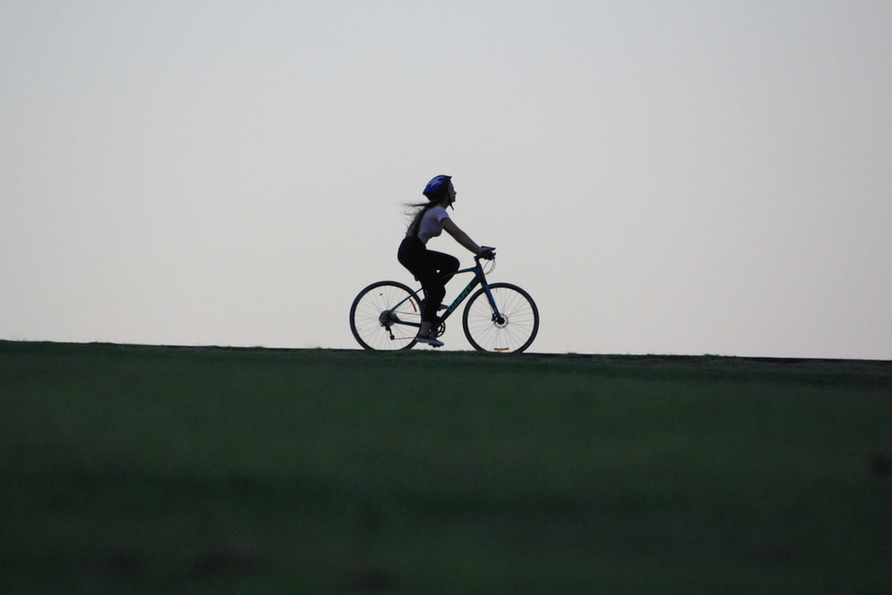 woman riding bike atop of hill