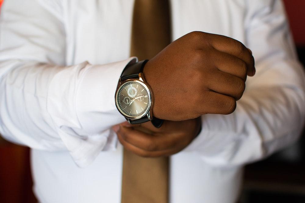 man wearing white dress shirt and black watch