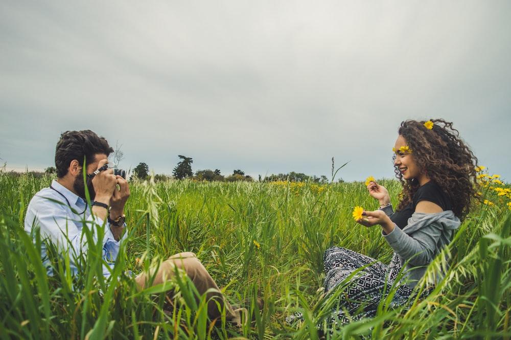 man taking photo of woman sitting on green grass