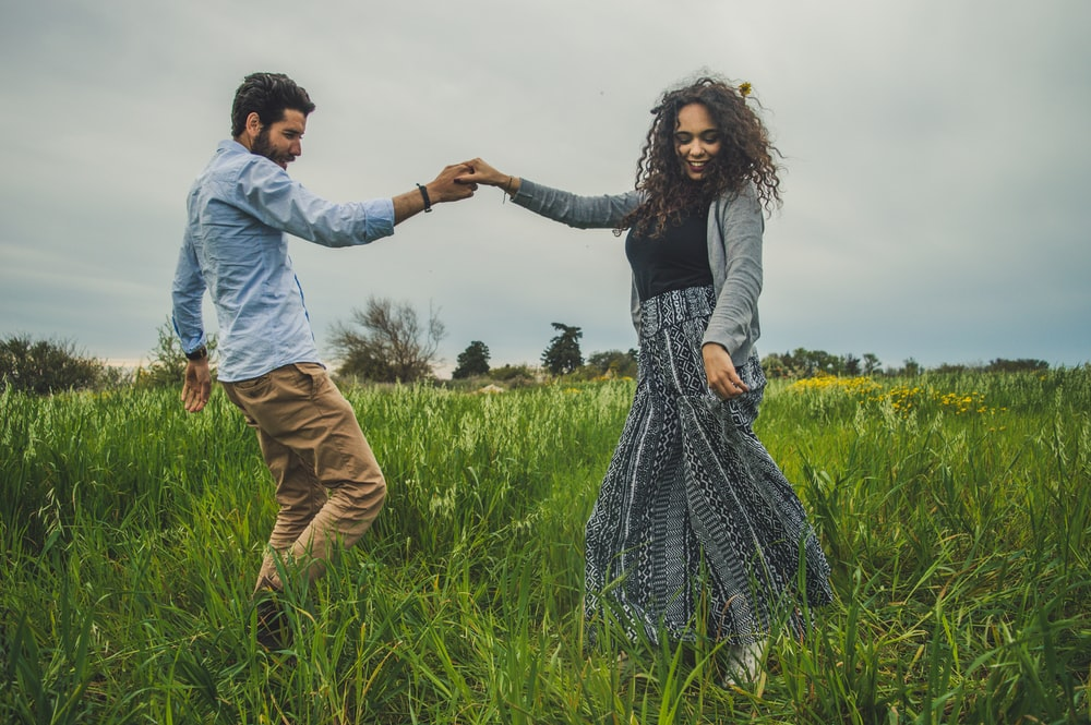 man and woman holding hands on green field