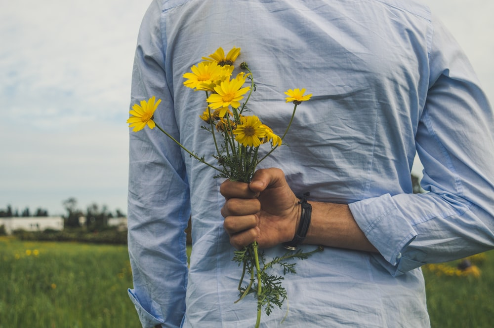 person holding yellow petaled flowers over his back