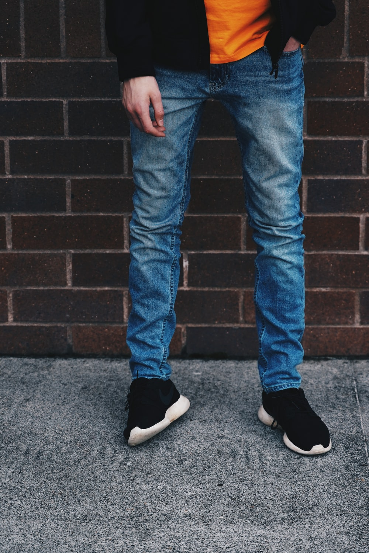 man in blue denim jeans standing