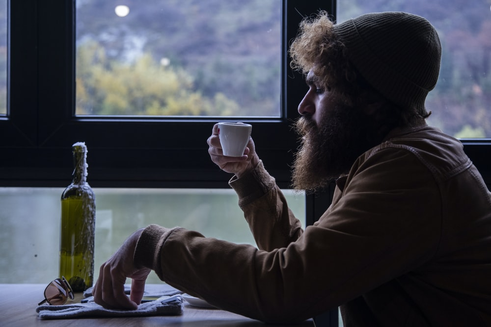 man holding white cup beside window
