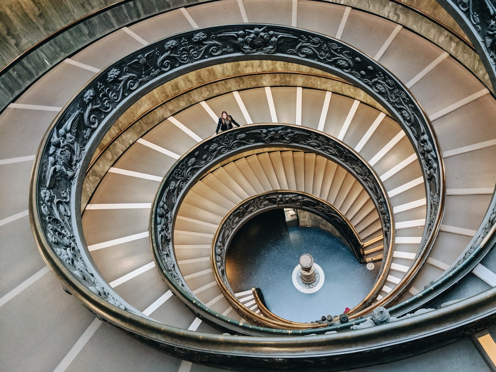 brown spiral staircase with brown wooden railings