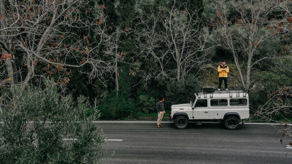 man standing in front of white Land Rover Defender SUV and other man standing on top of it during daytime