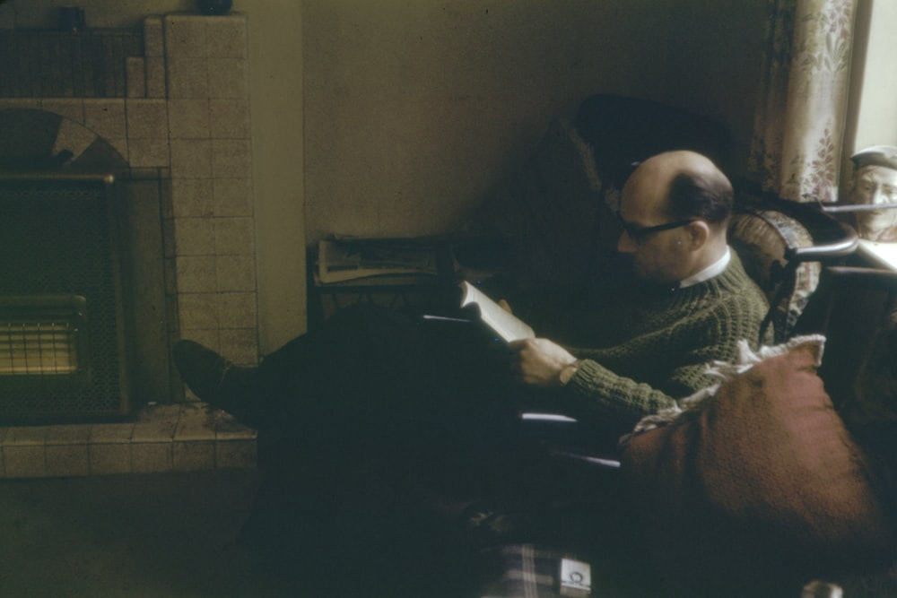 man sitting on sofa while reading book