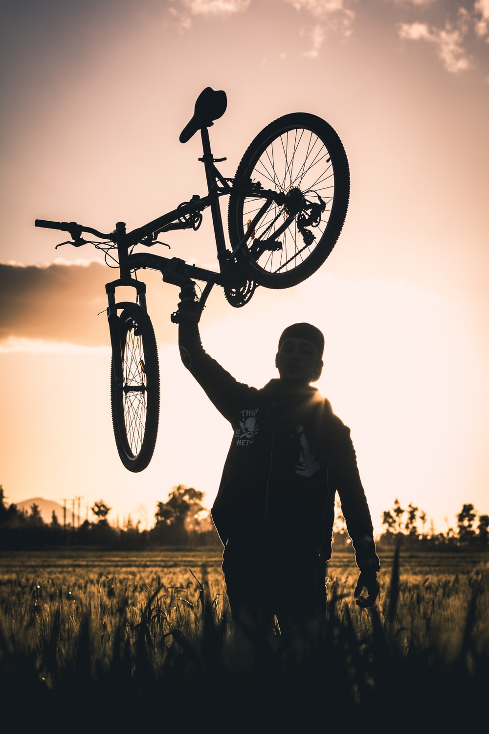 man carrying bike at frassfield during golden hour