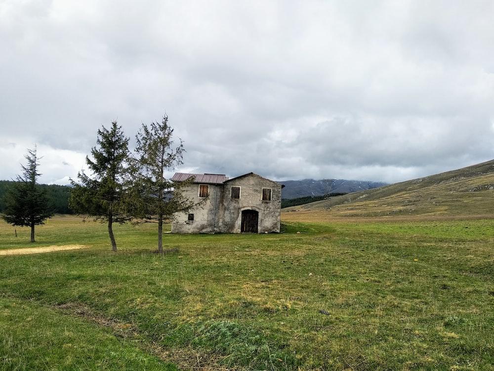 gray concrete house near green field