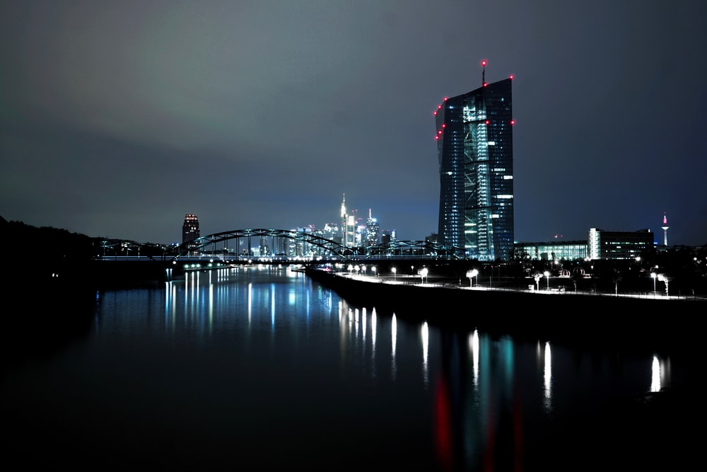 lighted high rise building near body of water at nighttime