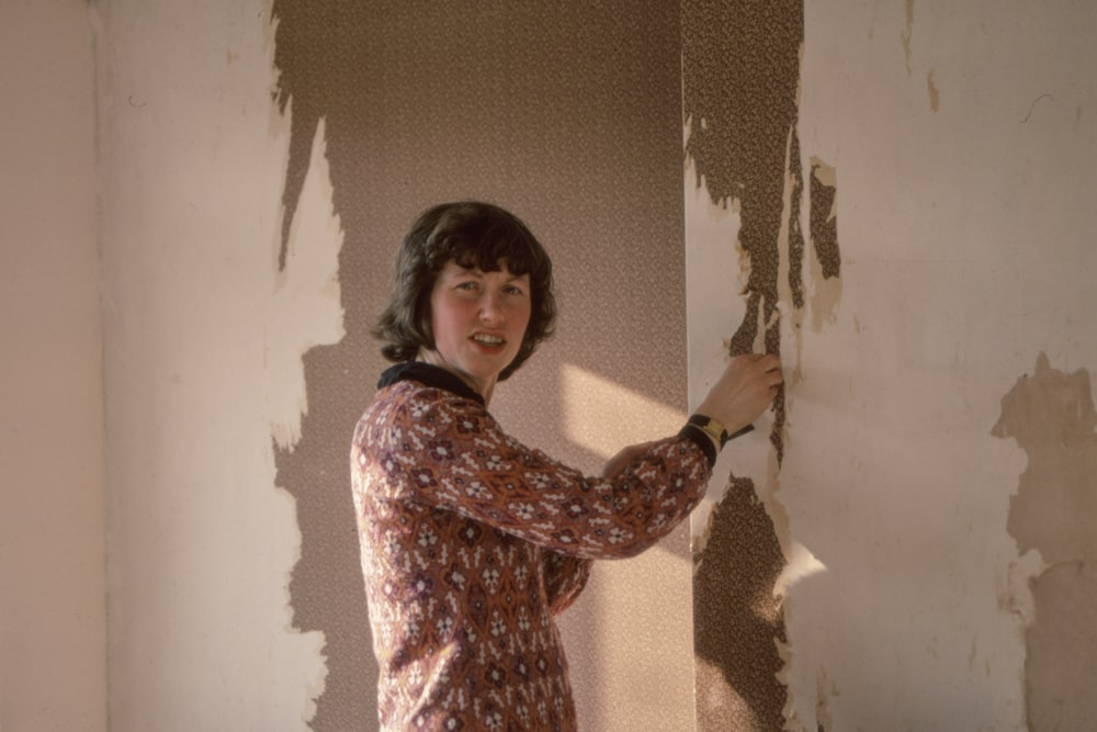 woman standing near brown wall