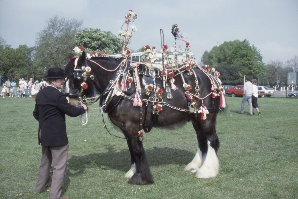 man standing beside black horse