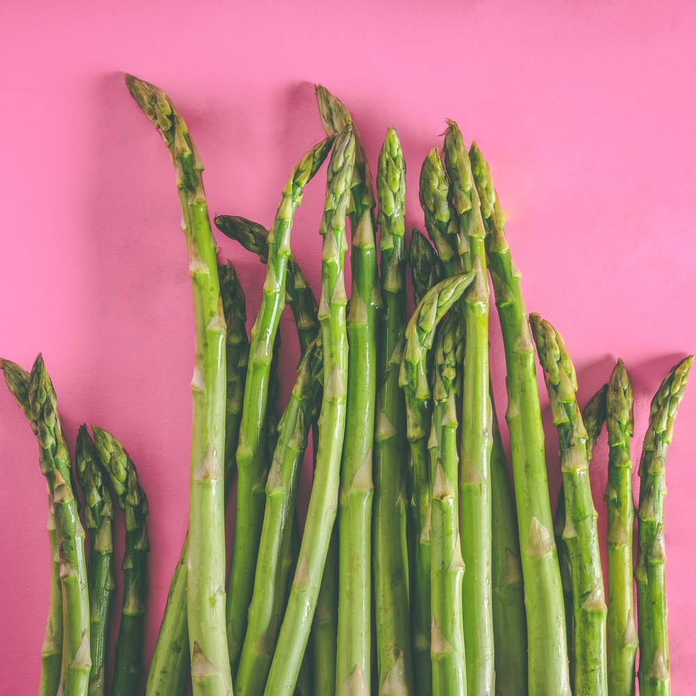 green asparagus vegetables on pink surface