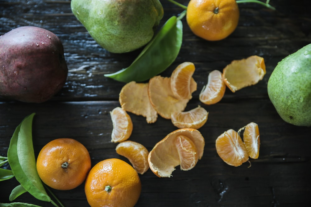 peeled oranges on table surround with other fruits