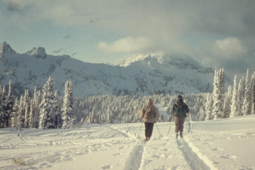 two people walking on snow field
