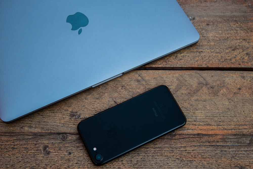 jet black iPhone 7 on brown wooden surface