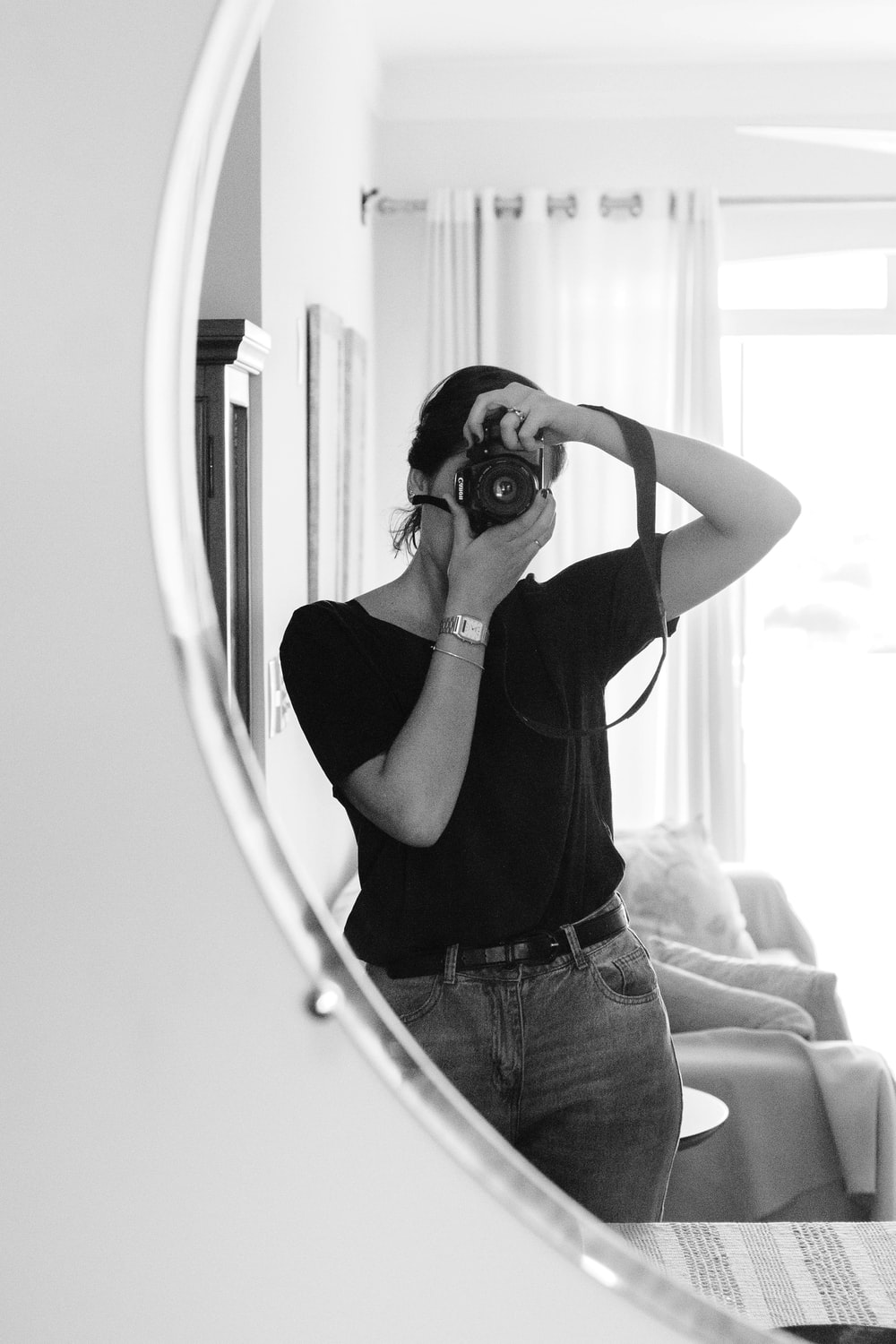 greyscale photo of woman taking photo on mirror