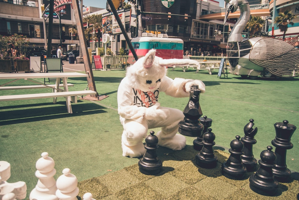 person wearing bunny costume playing lift-size chess