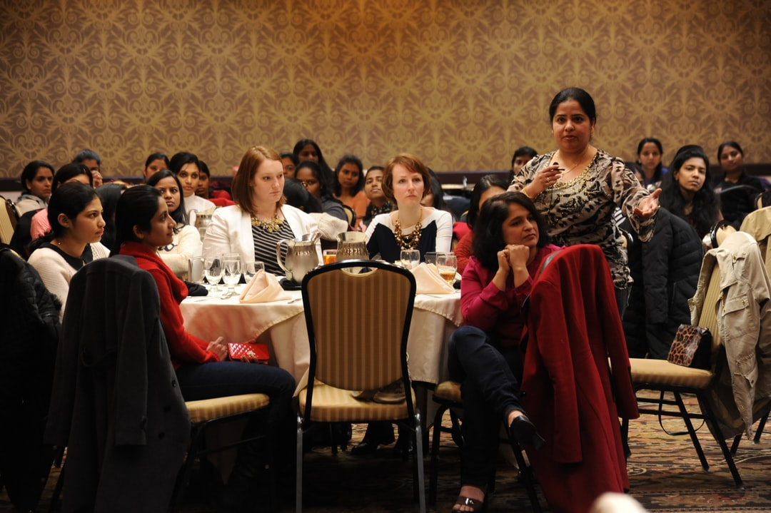 A woman asks a question of the CEO, Celebrating Women's Day, women who work in high tech, many from India, mostly working due to H1-B Visas, UX designers, PMs, coders, scripters, testers, attend a  lunch meeting (with former Infosys CEO visionary Dr. Vishal Sikka, out of frame), Bellevue, Washington, USA