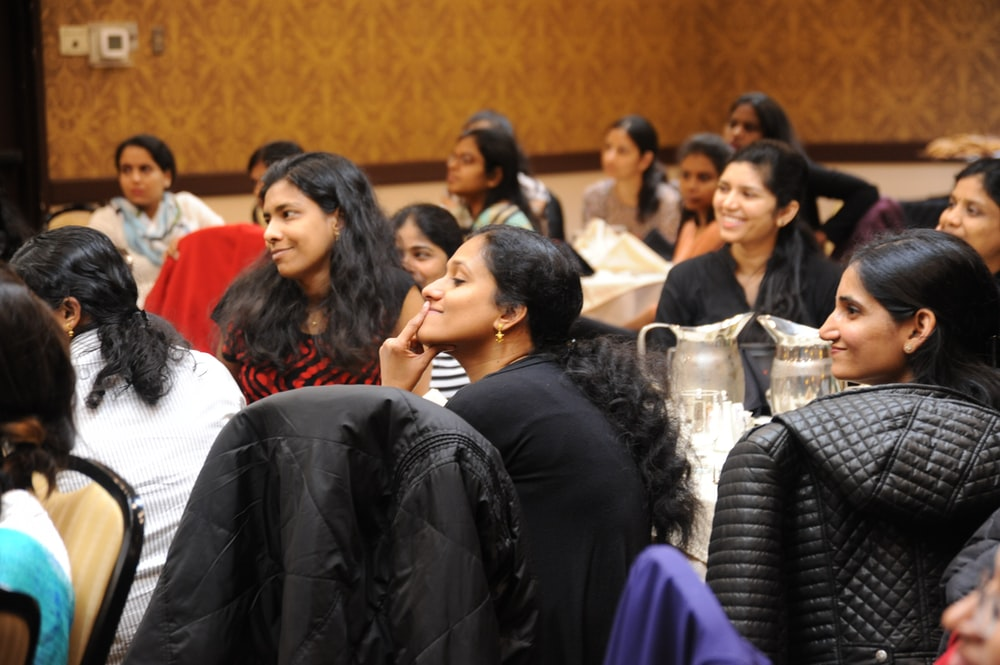 group of women sitting on chair while listening