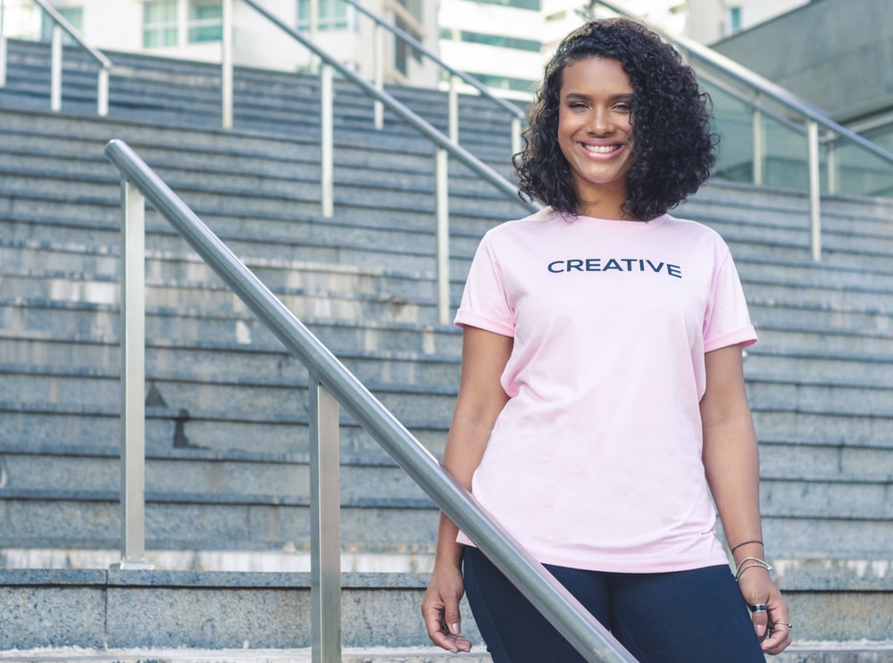 smiling woman in pink creative shirt standing on stairs by rails