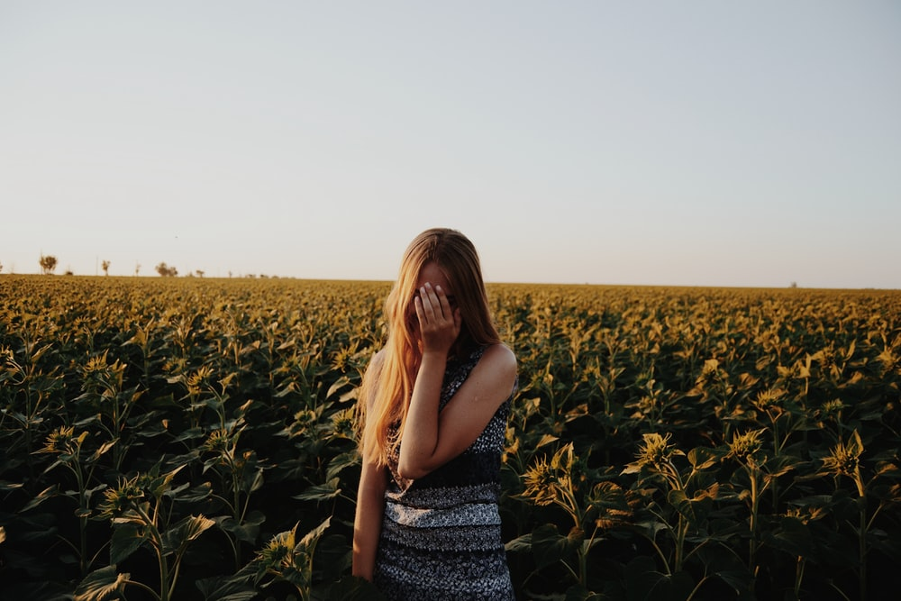 woman covering her face by hand standing on crop field