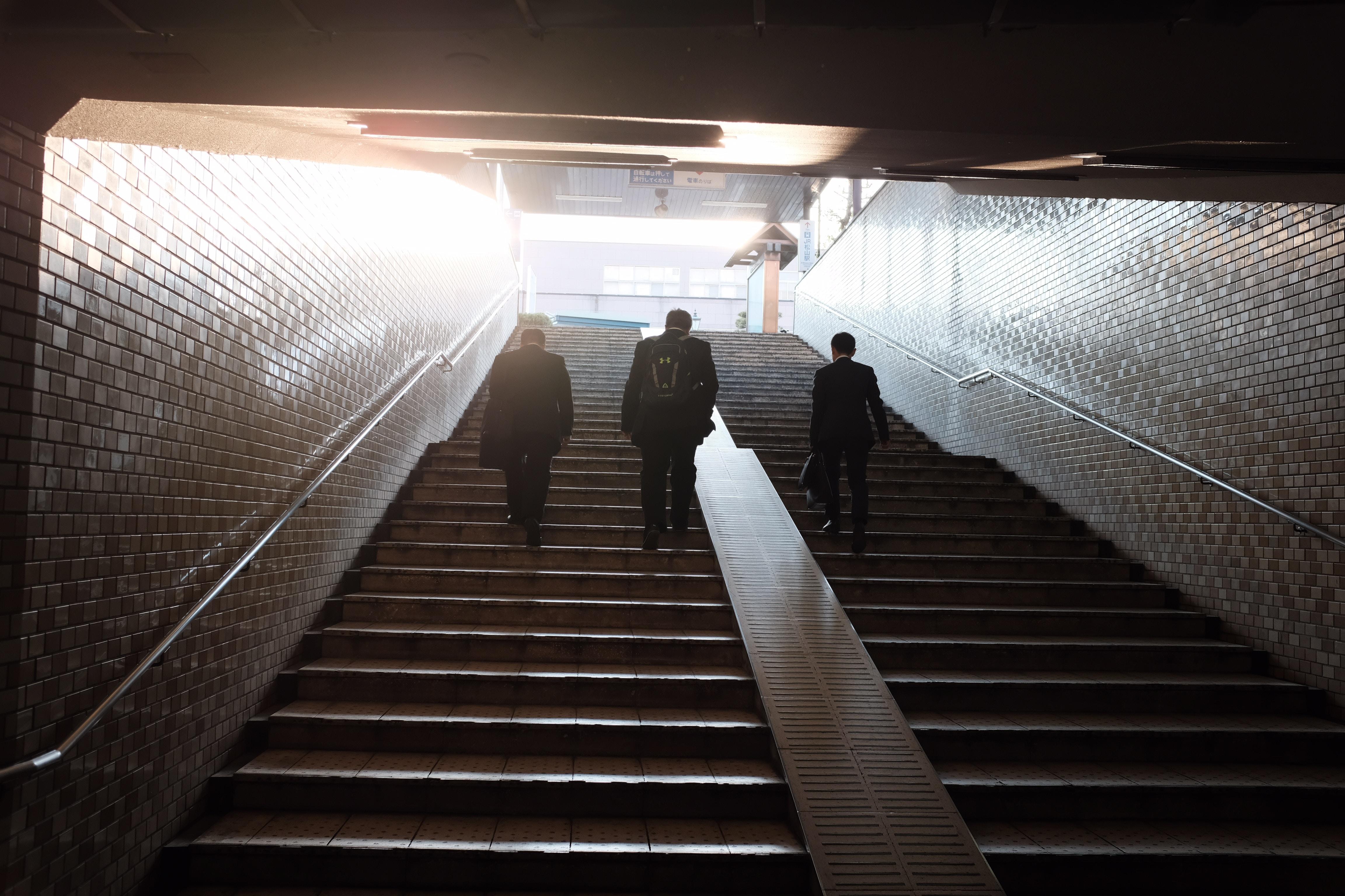 three man walking on stair