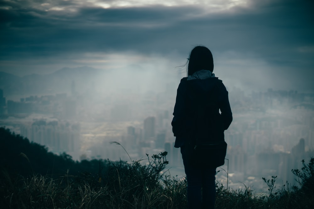 silhouette of person standing watching city