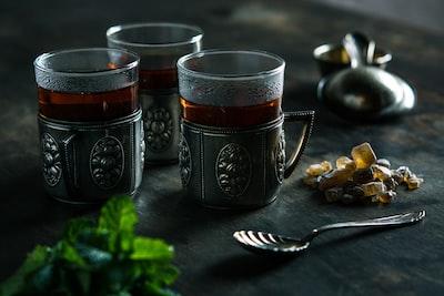 three clear glass mugs with brown liquid art noveau teams background