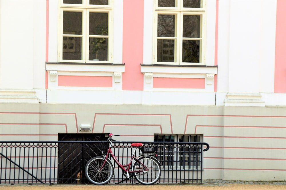 red bicycle parked in front of a pink and white building
