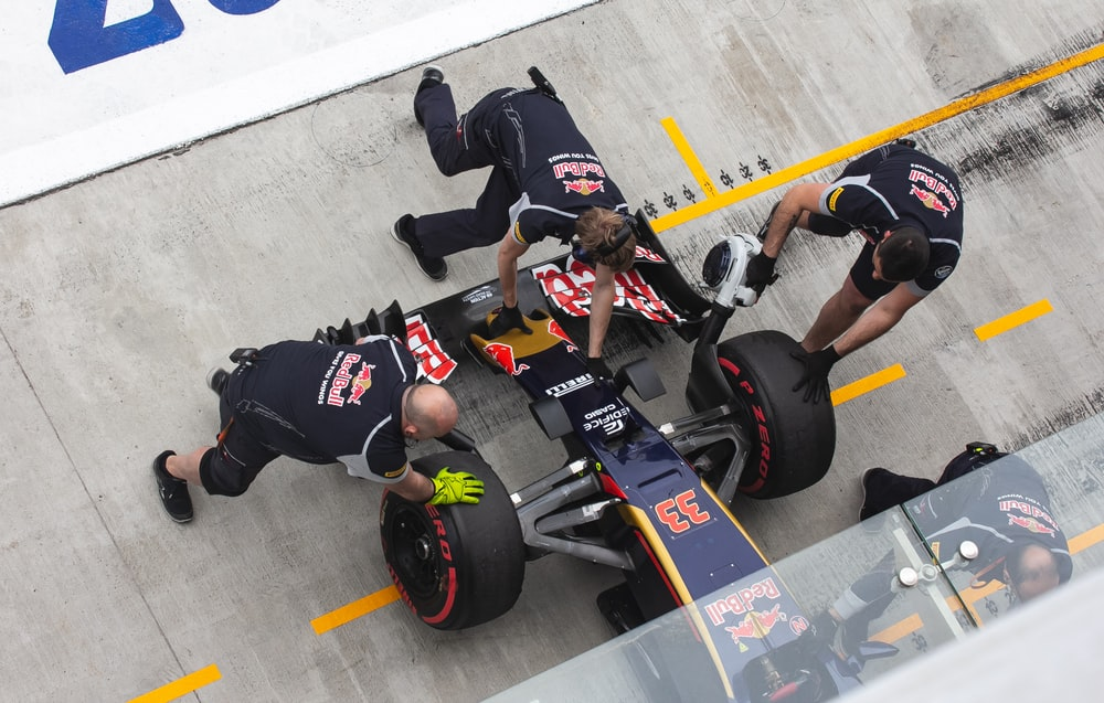 three men at pit stop fixing formula one vehicle