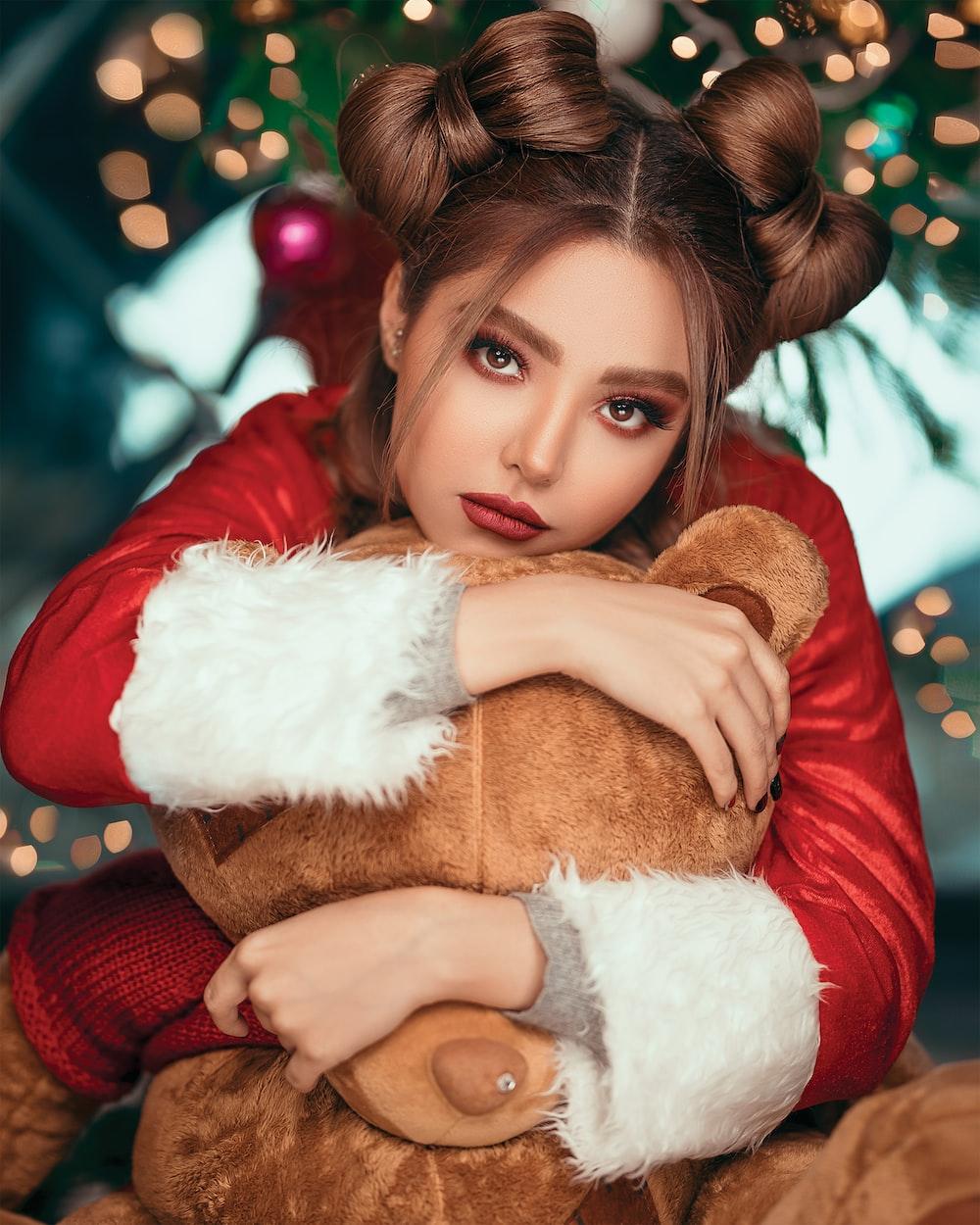 woman wearing red and white Santa costume hugging brown bear plush toy