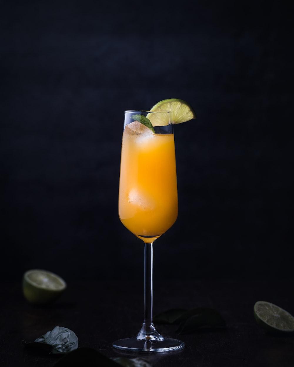 orange juice on clear glass