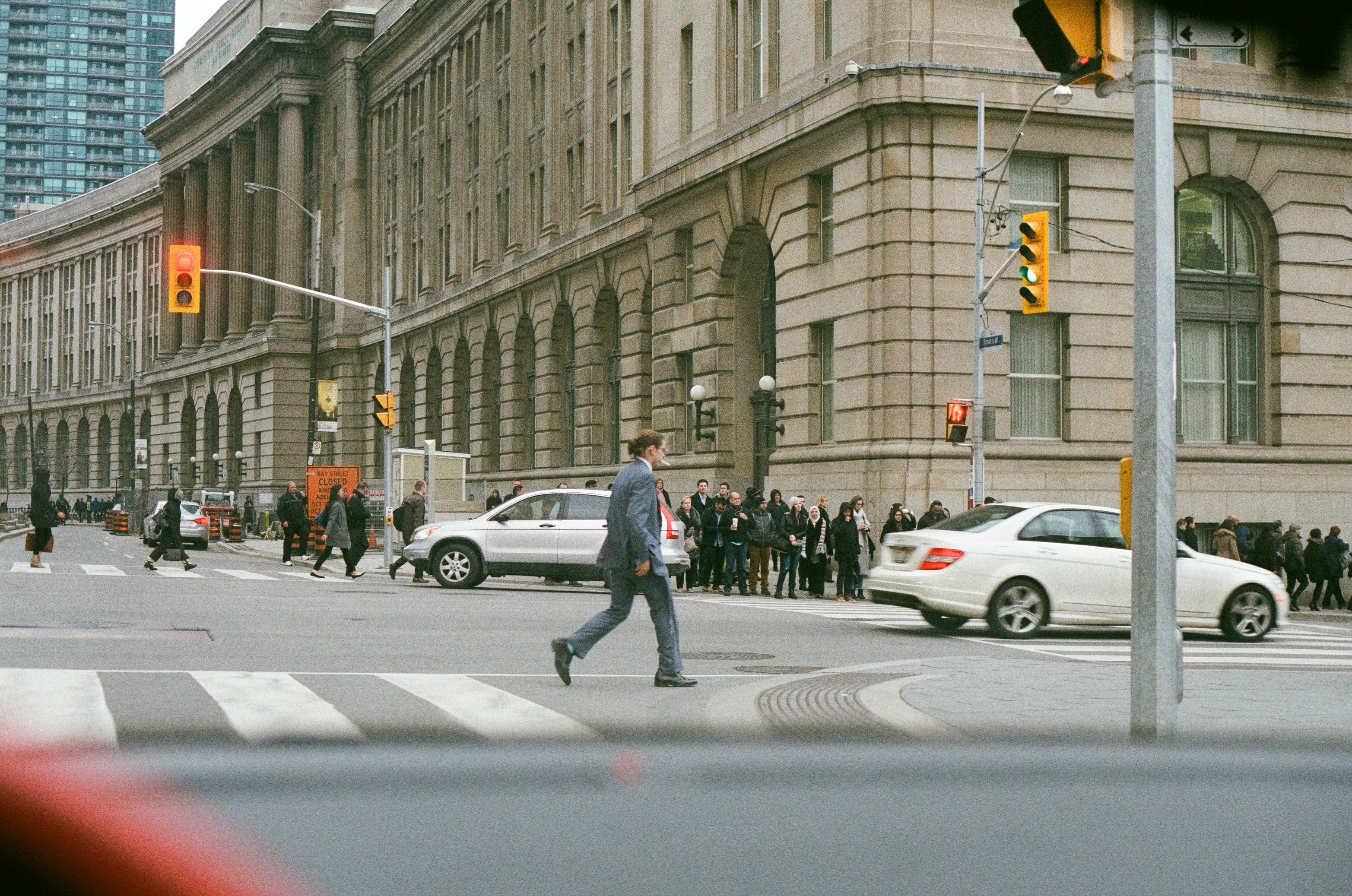 man in gray suit jacket and dress pants crossing pedestrian