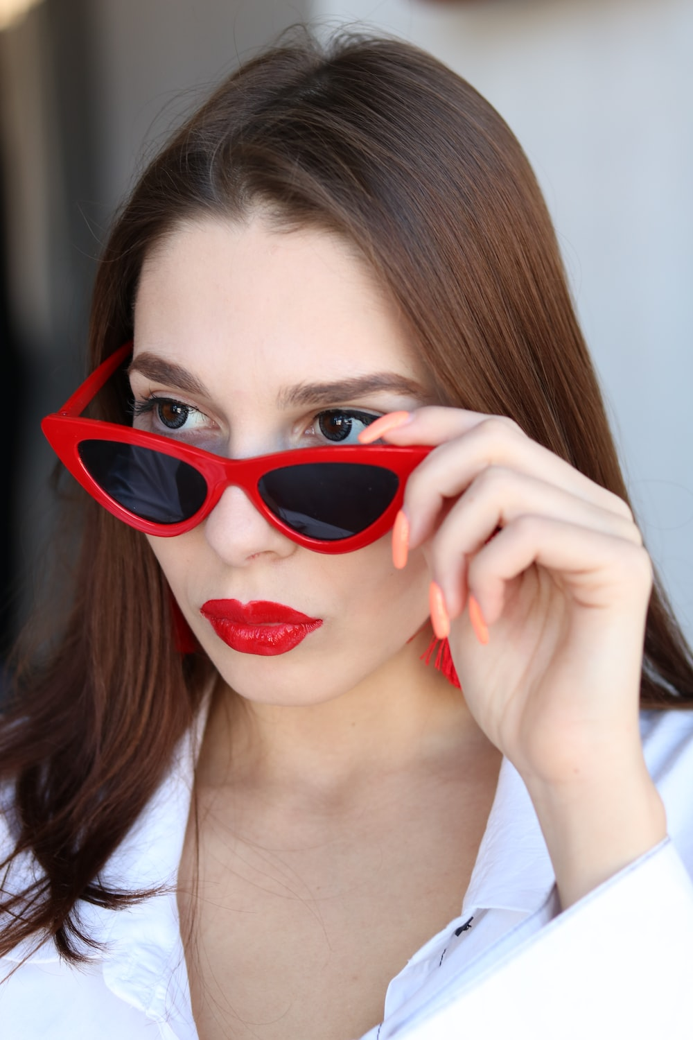 woman in white top about to wear off her red sunglasses