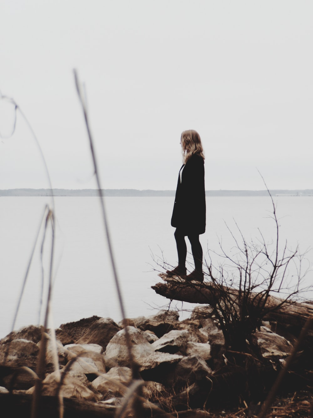 woman in black coat standing on log