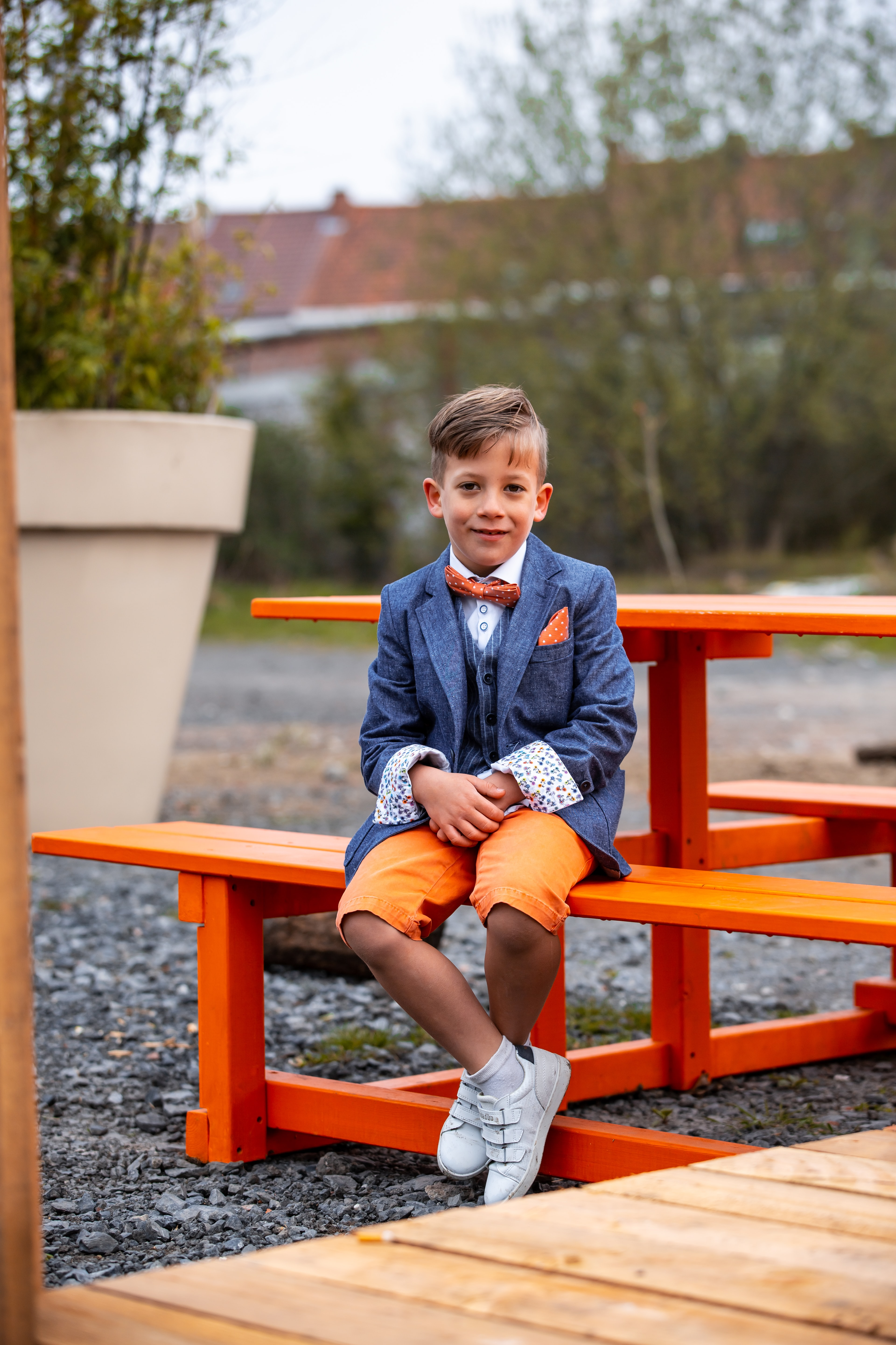 boy sitting on brown wooden picnic table