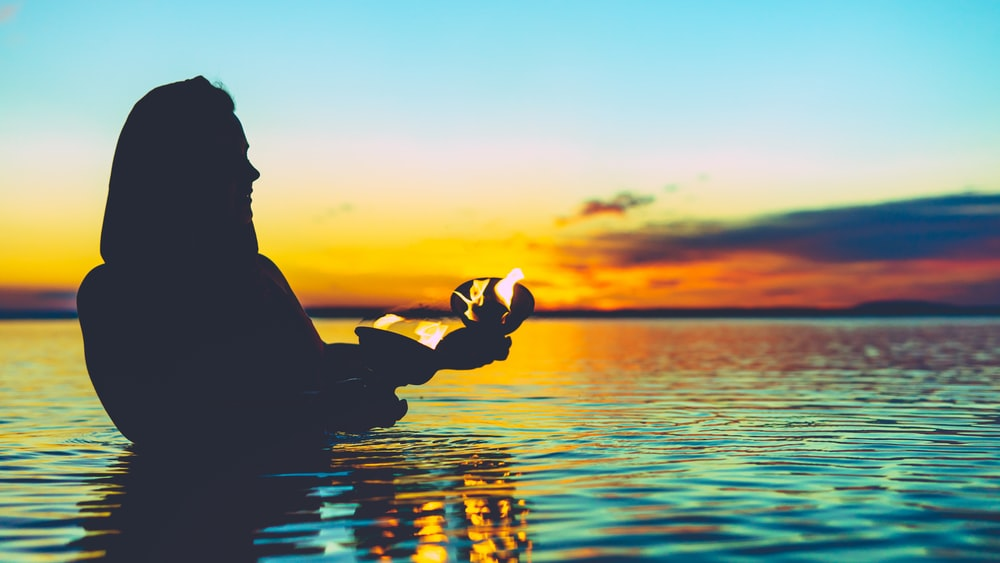 person in body of water holding pot