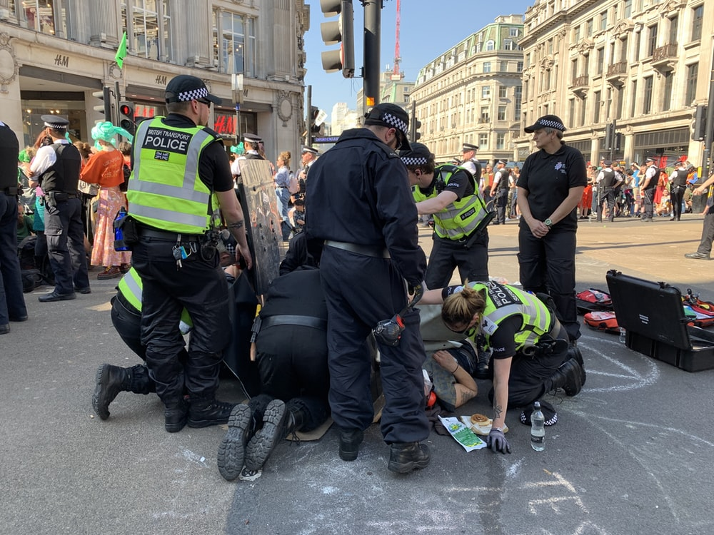 people rescuing man lying on ground