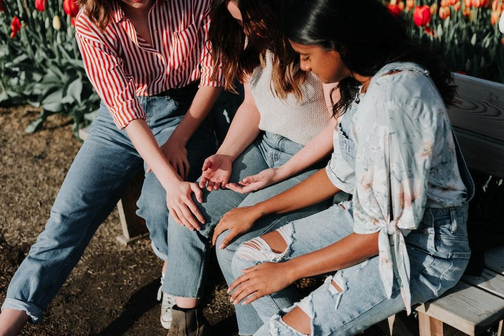 three women wearing blue denim jeans sitting on gray wooden bench