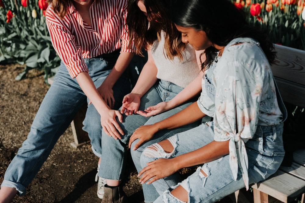 three women wearing blue denim jeans sitting on gray wooden bench