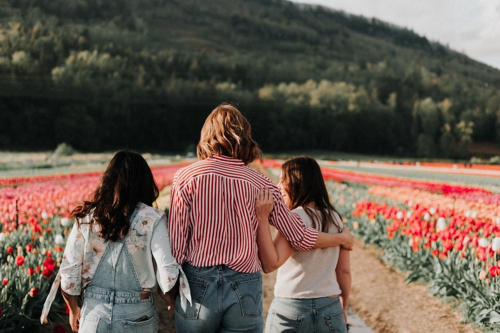 three women walking along field of tulip flowers